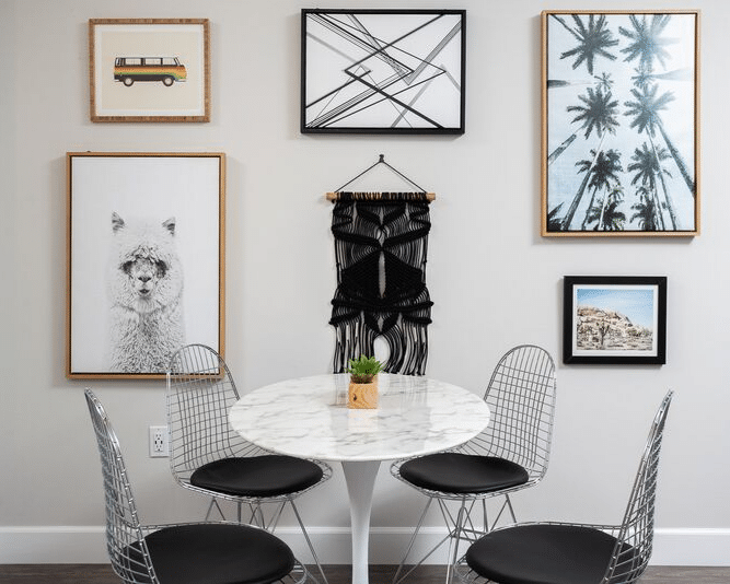 Dining area with table, metal wire chairs, and art work on the wall