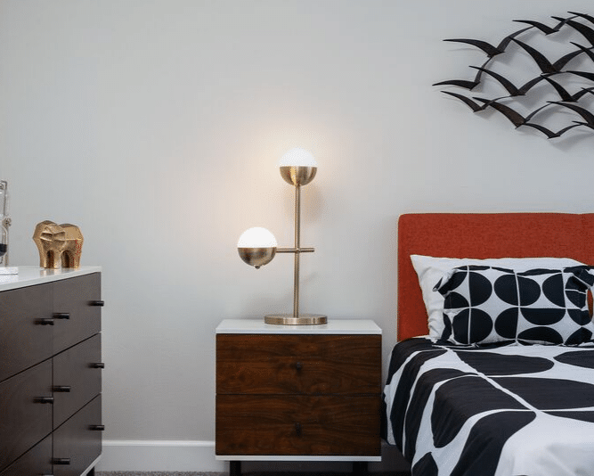 Bedside table with a lamp between a bed and a dresser with an elephant sculpture on top of it