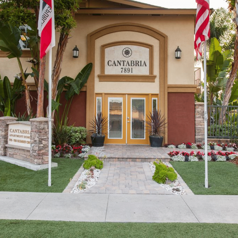 Cantabria Apartment Homes Entrance with sign, flags, and landscaping