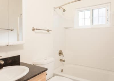 Empty bathroom with white tile and black countertop