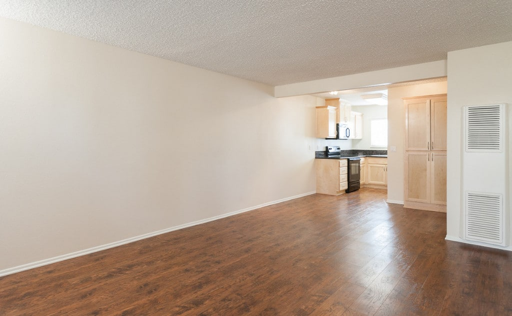 Empty living room and kitchen with wood flooring