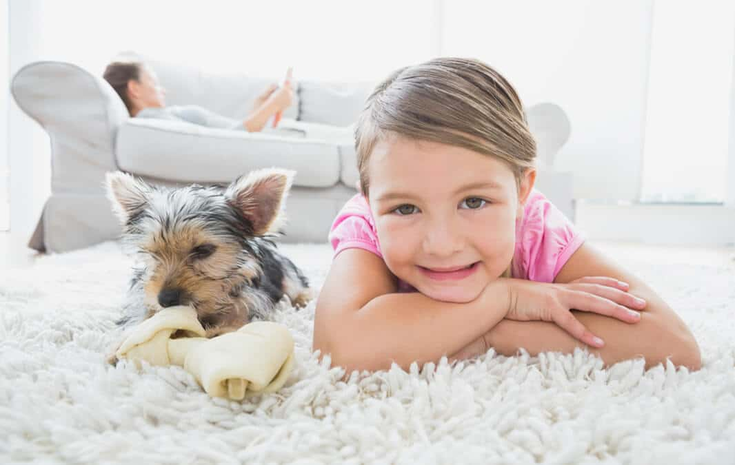 girl and dog lying next to each other on white rug